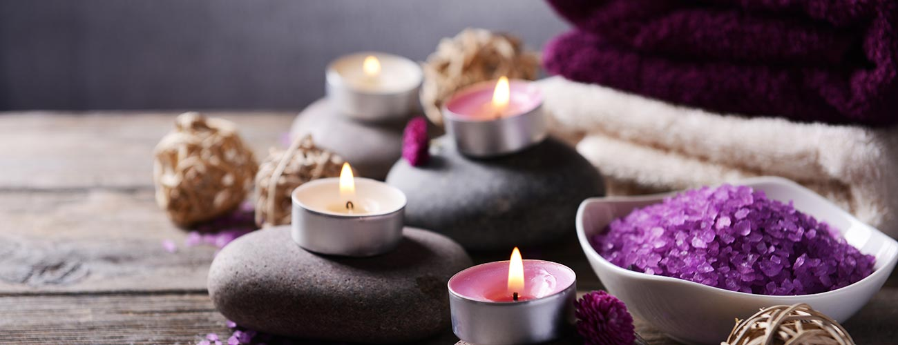 Black stones with burning candles and violet crystals as decoration of the wellness area