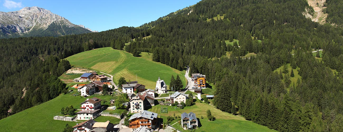 The Hotel Gran Mugon surrounded by woods on a hill in Vigo di Fassa
