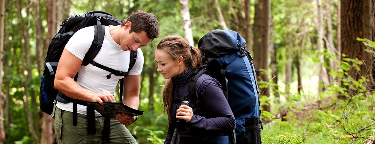 Couple with backpack looking at a hiking map in the woods
