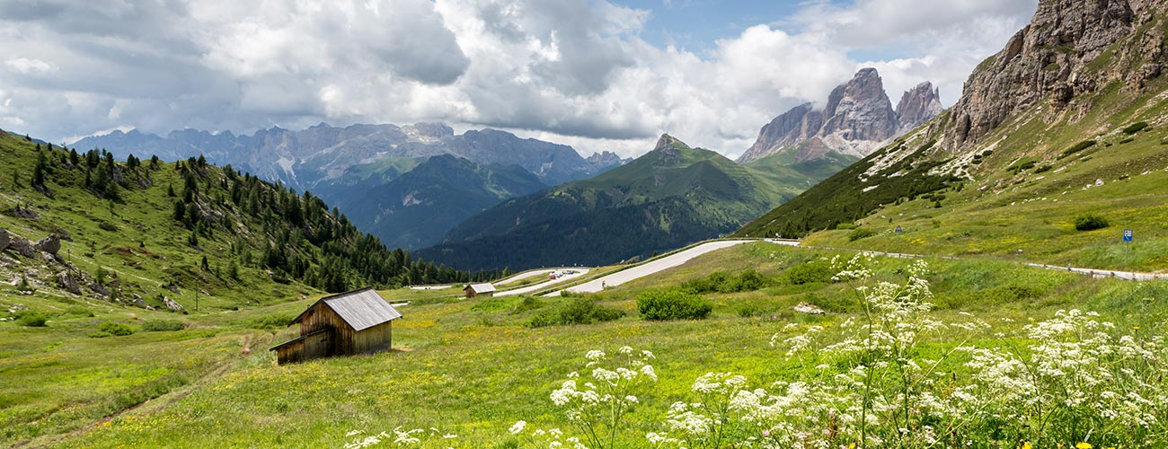 Panorama of Val di Fassa with pastures and low clouds