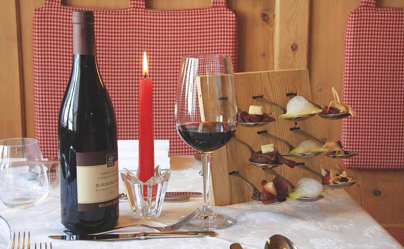 Burning red candle, bottle of red wine and filled red wine glass with finger food at the table