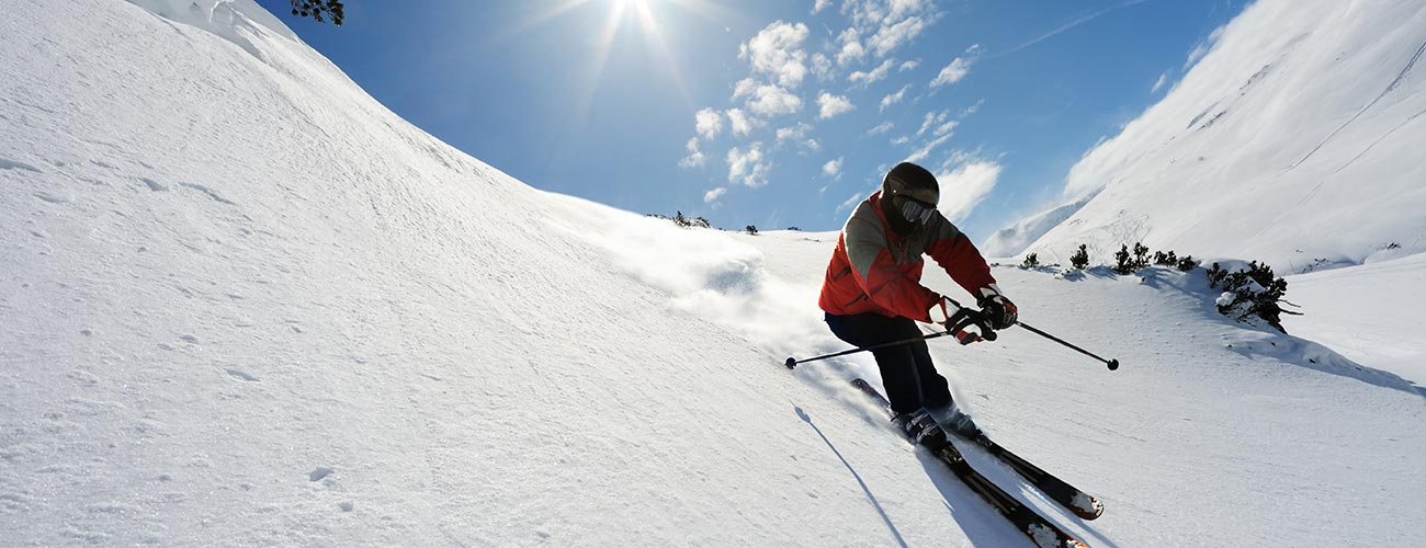 Skier in fresh snow during downhill down the piste