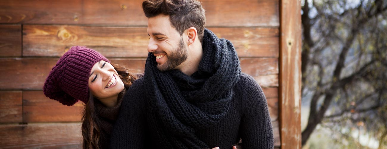 Couple in love with thick sweaters outside a wooden cabin in winter